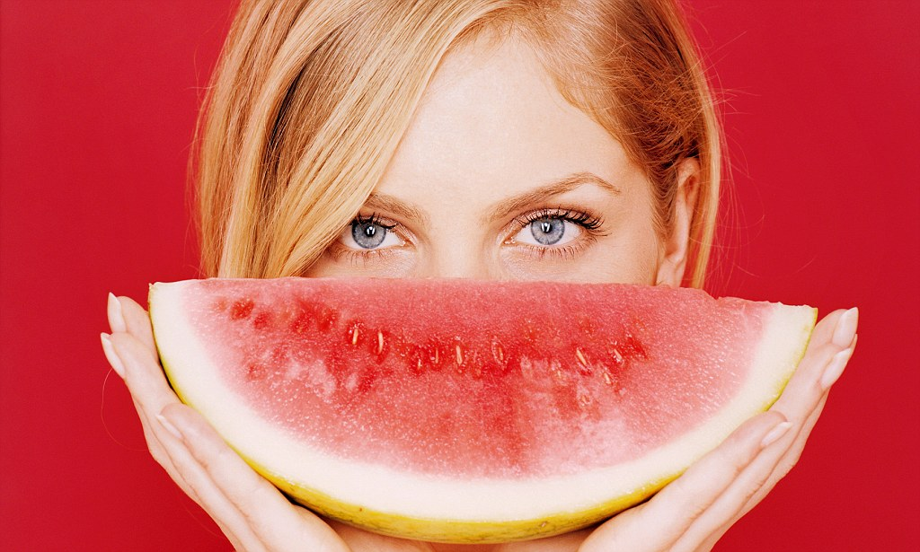 Young woman holding a slice of melon in front of her face --- Image by © Holger Scheibe/Corbis